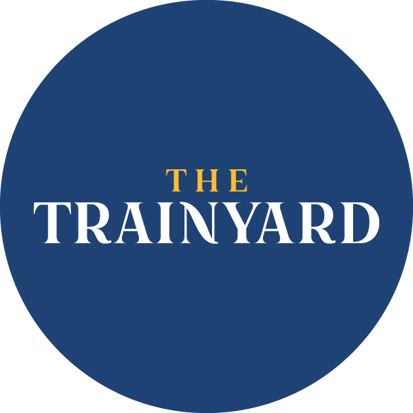 TheTrainyardBadge_Yellow_Blue